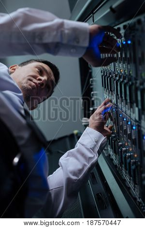 Telecommunication technology. Serious hard working professional programmer standing in front of the data server and doing his job while working with telecommunication technology
