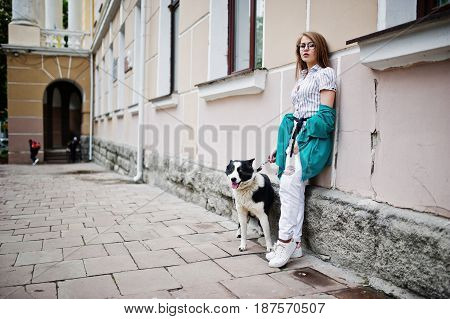 Trendy Girl At Glasses And Ripped Jeans With Russo-european Laika (husky) Dog On A Leash, Against St