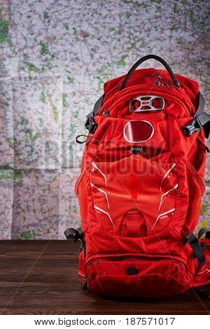 Orange big hiking backpack for the travelling against map background. Vertical photo of the rucksack. Travelling backgrounds and still-life. Planning and preparation of the trip. Concept of the active lifestyle.