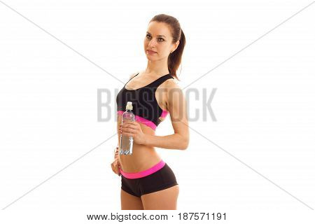 beautiful sport girl in short shorts and top stands sideways and holding a bottle of water isolated on white background