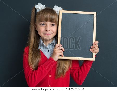 Happy pupil - cute girl posing with small blackboard in front of a big chalkboard. Back to school concept.