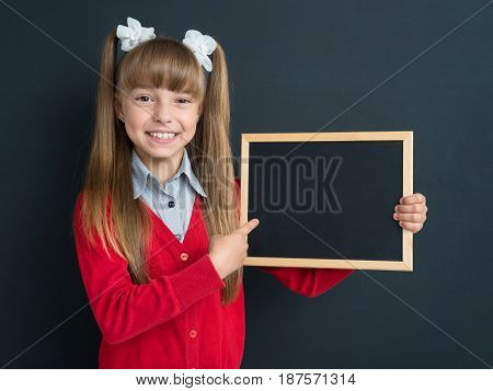Portrait of happy girl 10-11 year old with small blackboard in front of a big chalkboard. Back to school concept.