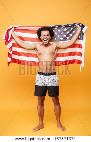 Full length portrait of a happy excited african man holding US flag over yellow background