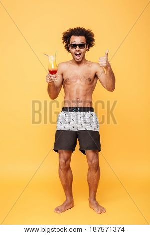 Photo of surprised young african man dressed in shorts standing isolated over yellow background. Looking at camera drinking cocktail and showing thumbs up.