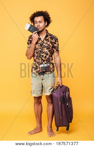 Picture of young sad african man standing isolated over yellow background. Looking at camera holding passport and suitcase.