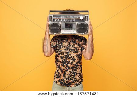 Image of young african man standing covering face with tape recorder isolated over yellow background.