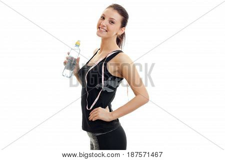 cheerful young fitness girl in black suit stands sideways smiles and holding a bottle of water and a measuring tape on the neck isolated on white background.