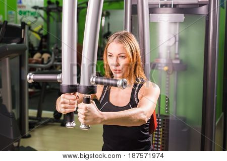 young fitness woman execute exercise with exercise-machine in gym, horizontal photo