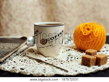 Cup of coffee on a table with knitting instruments