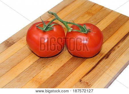 Close up of fresh tomatoes in drops of water on a wooden board.