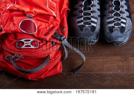 Top view of the tourist backpack and sportive shoes on the wooden boards. Equipment for the travelling. Bright orange rucksack. Horizontal photo with brown background. Planning and preparation for the trip. Concept of the active lifestyle.