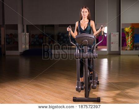 Beautiful gym woman exercising on a cardio machine smiling