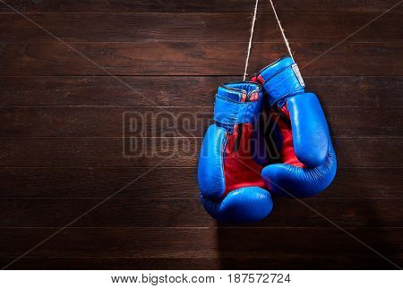 A pair of bright blue and red boxing gloves hangs against wooden background. Boxing backgrounds and still-life. Colorful accessories for sport. Horizontal photo. Training and sportive exercise. Concept of the active and healthy lifestyle.