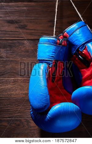 Blue and red boxing gloves hanging on wooden wall. Vertical photo of the colorful sportwear. Brown wooden background. Sportive training and exercise. Boxing backgrounds and still-life. Concept of the active lifestyle.
