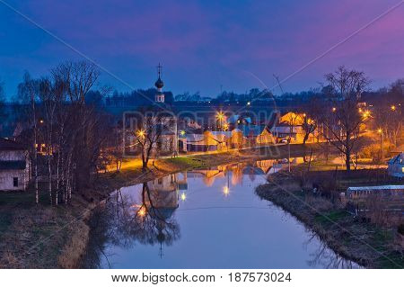 Night view of old Russian town Suzdal, reflection in Kamenka river