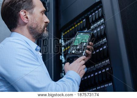 Collecting data. Hard working nice serious man holding a hard drive and looking at it while working as an IT administrator