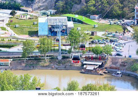 Tbilisi, Republic of Georgia - April 29, 2017: Tbilisi red cable car cabins and aerial city skyline panoramic view and Mtkvari or Kura river