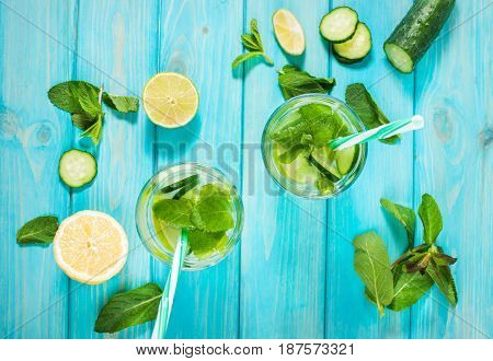 Cold and refreshing infused detox water with lime mint and cucumber in a glass on wood background. Top view