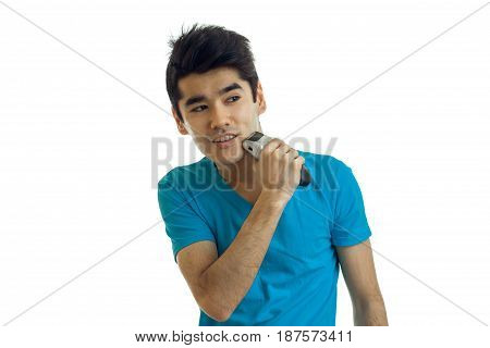 attractive young guy with black hair is smiling looks away and shaves his beard is isolated on a white background
