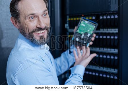 Great mood. Cheerful delighted nice man holding a hard drive and smiling while enjoying his job