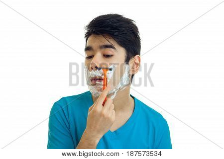 Portrait of ridiculously handsome guy who carefully shaves mustache machine is isolated on a white background