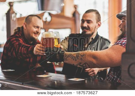 Strong friendship. Cheerful men sitting in pub and toasting beers. Focus on hands with mugs