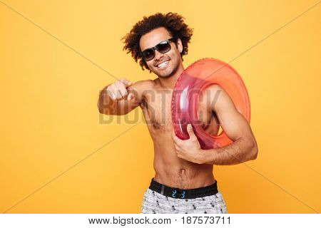 Portrait of a happy cheerful afro american man in summer shorts holding inflatable ring and pointing finger at camera over yellow background