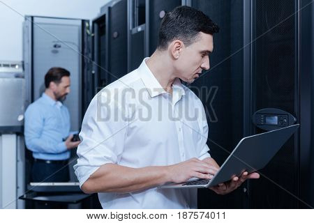 Modern data center. Handsome pleasant young technician holding a laptop and looking at the control panel while checking the security system