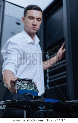 For information storage. Selective focus of a hard drive being taken by a professional male technician while working in the server room