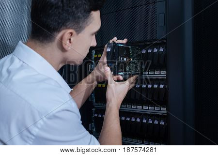 Data security. Nice handsome male technician holding a hard drive and putting it into the data server rack while doing his job