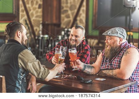 Meeting with best friends. Positive bearded men in casual wear holding glasses with beer. They sitting at table in pub and smiling
