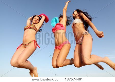 The company of young slender girls in colored hats and bathing suits jumps into the sky on the beach. Rest, sun and sea