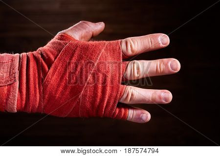 Close-up image of boxer's hand with a red bandage against brown background. Horizontal photo and wooden wall. Sportive backgrounds. Boxing exercise and training. Concept of the sportive lifestyle.