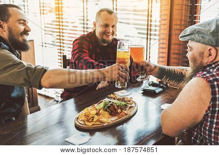 Meet of best friends. Three cheerful bearded men in casual wear toasting with cool beer. They sitting at table in sports pub