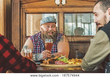 Enjoyable time. Joyful positive friends laughing and drinking beer while sitting at table in pub. Fat bearded man holding glass while looking at camera with smile