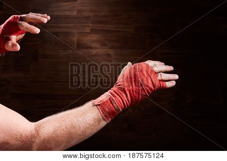 Hands of muscular athletic man with red bandage against brown background. Horizontal photo and wooden wall. Boxing backgrounds. Sportive exercise and training. Concept of the sportive lifestyle.