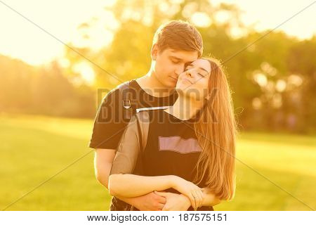 A loving couple hugs in the park at sunset
