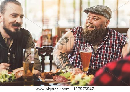 Interesting story. Cheerful old friends having fun together while watching football and drinking beer in pub. Focus on fat bearded tattooed man