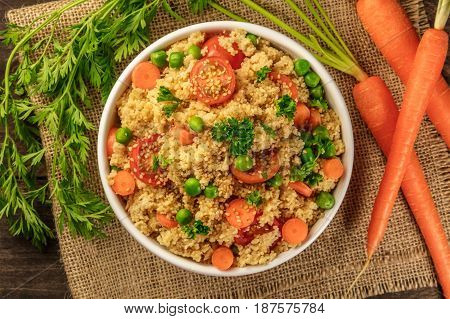 An overhead photo of a vegetable couscous with parsley, cherry tomatoes, and green peas, with fresh carrots, on rustic textures