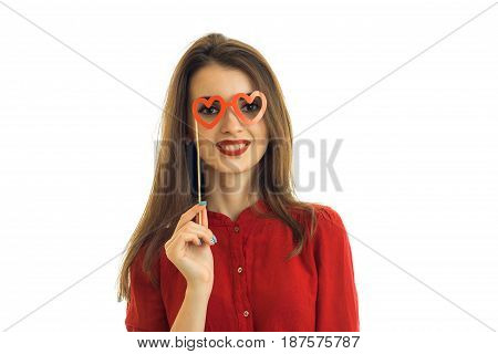 beautiful young smiling girl stands in front of the camera and holds near eye paper glasses isolated on white background