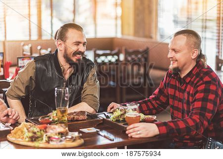Friendly talk. Two stylish bearded men laughing while having dinner together. They sitting in pub and communicating while drinking beer