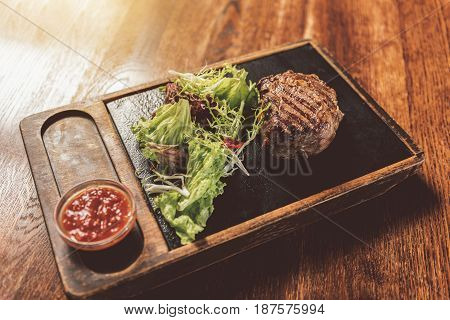 Best dish. Close-up of tasty grilled beef medallions with tomato sauce and mix salad. Wooden table in the background