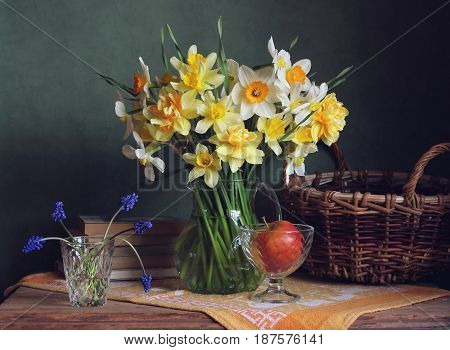Bouquet of yellow daffodils in a clear pitcher Apple and books on the table. Still life.