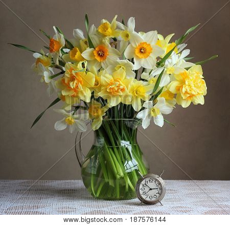 Bouquet of yellow daffodils in the transparent jug and retro alarm clock on table with white tablecloth. Still life.