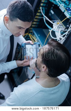 Technological issues. Top view of nice handsome professional engineers standing near the data server and discussing their work while looking at each other