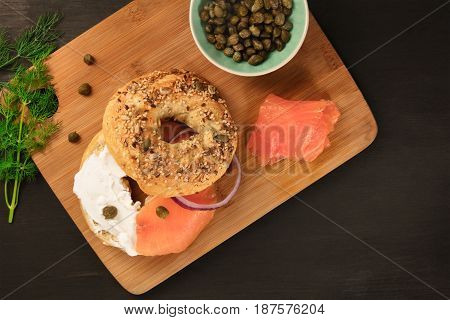 A photo of a bagel with cream cheese and lox, with a purple onion ring, a sprig of dill, and capers, shot from above on a black texture with a place for text
