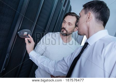 Limited access. Serious young male technician entering a code and pressing a button on the control panel while standing with his colleague