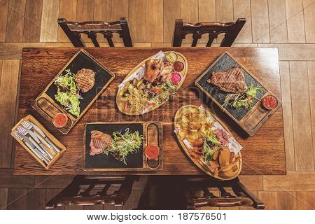 Hearty dinner. Top view of variety of tasty dishes are on table. Assortment of grilled meat meals