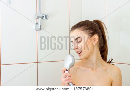 beautiful gentle girl sings in the shower closing eyes closeup