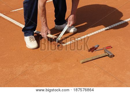 Worker Repairing lines on a tennis court